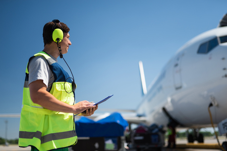 Checking the jet. Side view of airport crew member. Man wearing headphones and holding the clipboard Stock Photo