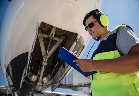 Doing paperwork. Low angle portrait of man in sunglasses filling out documents while standing near passenger plane Stock Photo