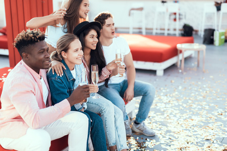 Positive ladies communicating with smiling men. Happy comrades relaxing on cozy sofa while drinking alcohol liquid outdoor