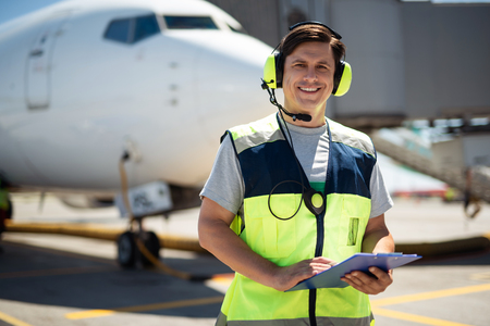 Time for fun. Waist up portrait of smiling worker at airport. Man holding clipboard and wearing headphones with microphone