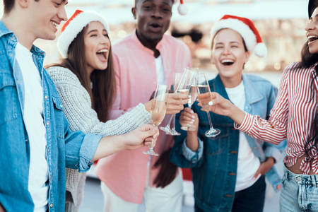 Laughing girls and beaming men speaking while drinking glasses of champagne. They wearing red hats during new year celebration Banco de Imagens