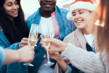 Optimistic ladies and cheerful men drinking glasses of delicious champagne while telling together. Happy friends celebrating new year concept Stock Photo