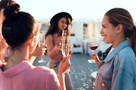 Optimistic ladies drinking alcohol liquid while talking together outside. They holding glasses in hands Stock Photo