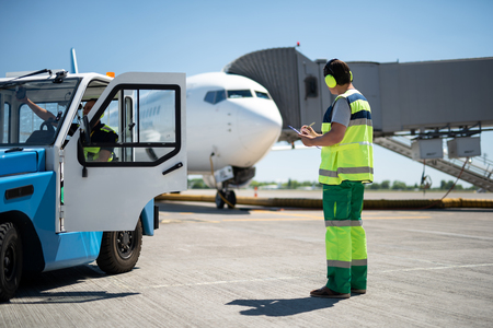 Excellent teamwork. Full length portrait of man looking at aircraft and writing information while coworker checking the vehicle
