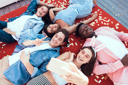 Top view portrait of cheerful males and happy ladies looking at camera while resting together on modern sofa. Pleased girl and outgoing guy gesticulating hands while doing photo on phone