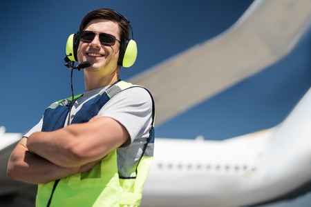 Nice shot. Low angle portrait of ground crew member smiling and posing near passenger plane. Copy space in right side Stock Photo