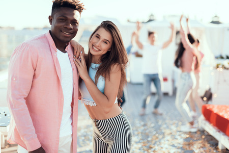 Portrait of outgoing woman hugging satisfied man while situating on modern party with friends