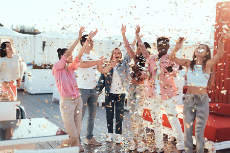 Satisfied ladies and beaming males catching confetti while having fun during funny party outdoor