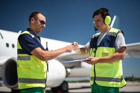 Teamwork at airdrome. Man in sunglasses taking pen and documents for signing while colleague holding clipboard. Blue sky and passenger plane on blurred background