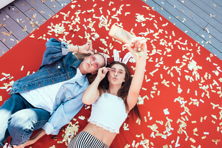 Top view portrait of satisfied women watching at mobile while taking selfie on contemporary mobile. They having leisure on comfortable couch. Positive comrades spending time together concept Stock Photo