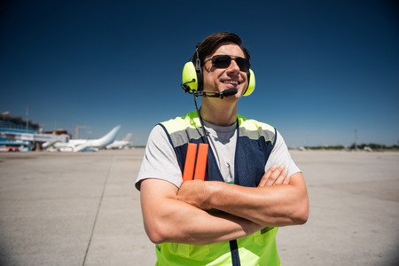 Enjoying beautiful sunny day. Waist up portrait of smiling man in headphones and sunglasses. Blue sky, runway and planes on background Stock Photo
