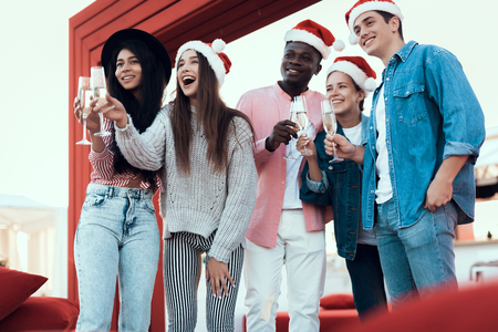 Portrait of cheerful young women and outgoing men drinking glasses of champagne during christmas party