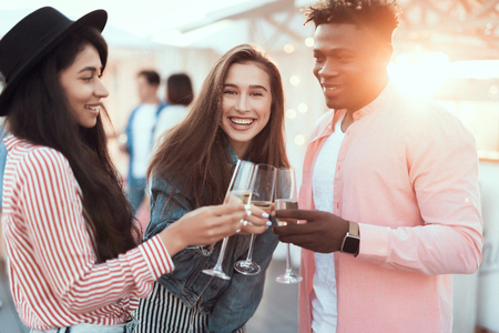 Cheers. Happy girls and smiling man telling while enjoying glasses of champagne during party