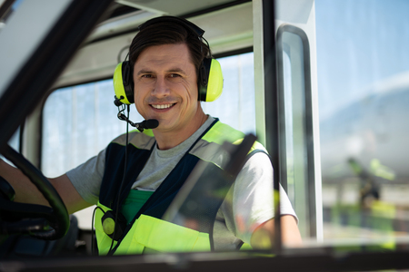Joyful working day. Positive man in headphones with microphone posing in the car during work at airport. He is looking at camera with happy smile. Blurred background