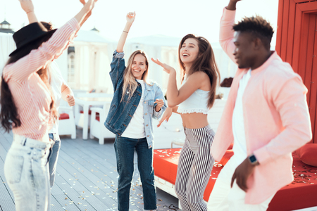Pleased women and optimistic males gesticulating hands while having fun during party outdoor
