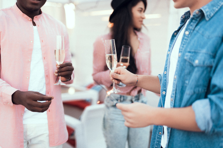 Two male and outgoing lady tasting glasses of delicious champagne while communicating during party