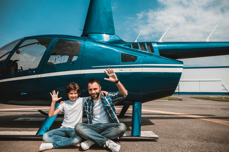 Full length portrait of smiling kid and positive unshaven man gesticulating hands while resting near helicopter outside