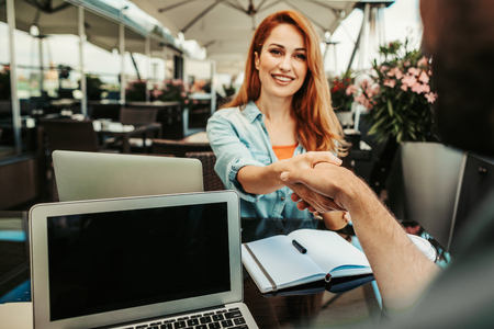 Glad to see you. Smiling young lady shaking hands with gentleman. Couple sitting at the table with laptops and notebook Banco de Imagens
