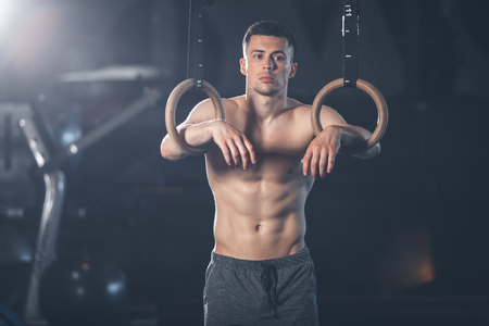 Brooding man is standing and leaning on sport rings. He is resting after acrobatic training with outfit un sport center. Topless shredded guy is looking away considering something