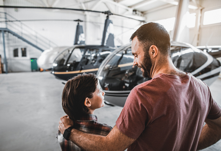 Side view optimistic kid communicating with beaming bearded dad while standing opposite helicopters. Glad parent embracing boy