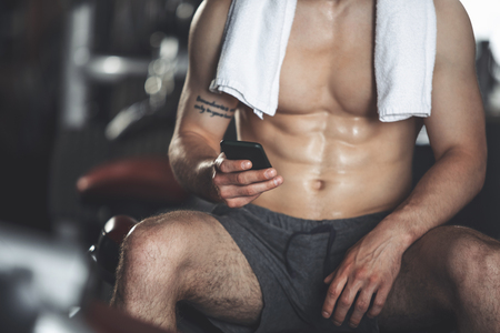 Close-up of male torso while doing sport. He is sitting on machine bench while being topless and having towel on shoulders. Man is typing on his smartphone