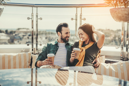 We are in love. Happy bearded man looking at pretty young lady while hugging her. They are holding cups of coffee and smiling