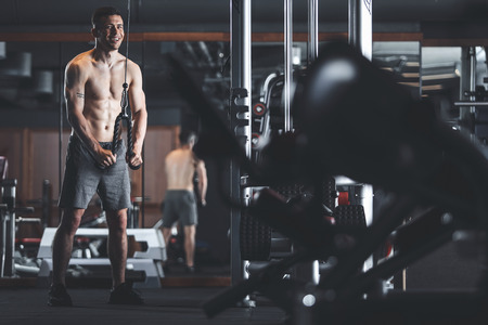 Focus on smiling topless athlete while exercising in sport club. He is standing near machine and pulling down cable with weight for triceps relief. Copy space in right side