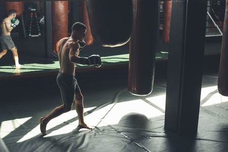 Strong guy is improving combat skills in sport studio. He is jumping and hitting punching bags. Copy space in right side