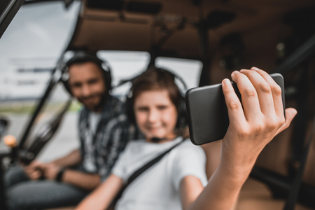 Portrait of glad kid keeping contemporary mobile in hand while doing felfie with positive dad. They having fun in rotor plane