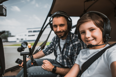 Portrait of satisfied unshaven man and cheerful boy wearing contemporary earphones while looking at camera. They having leisure in rotor plane as pilots