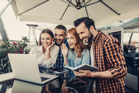 Hello there. Smiling young ladies and bearded men looking at laptop. Company sitting at the table with smartphones