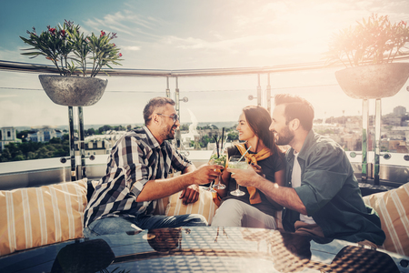 Feeling joyful. Bearded men and lovely young woman sitting at the table with alcohol drinks in their hands. They are toasting and laughing Banco de Imagens