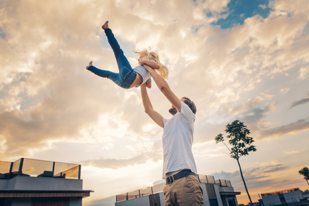 Laughing male throwing in air smiling little daughter outdoor. Happy dad having fun with cheerful child during rest outdoor concept