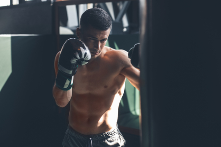 Shirtless shredded guy is having combat training in gym. He is kicking punching bag while wearing gloves. Male is concentrated on fighting Reklamní fotografie
