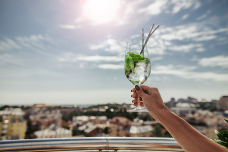 Cheers. Woman arm with fresh mojito on blurred background 免版税图像