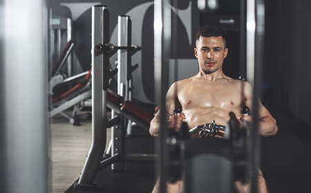 Focus on joyful sportsman exercising on horizontal row machine in sport center. He is working on back muscles while using heavy weights. Copy space in left side 免版税图像