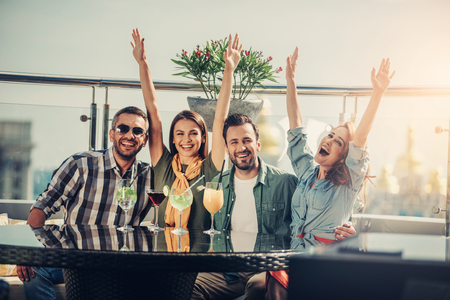 We are happy. Two couples spending time at rooftop bar. Smiling bearded men hugging lovely girls while ladies raising hands and laughing Stock Photo