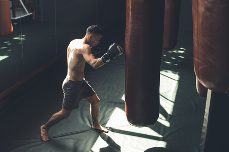 Top view of shredded topless man boxing with punching bag. He is having hard cardio workout with outfit. Copy space in right side