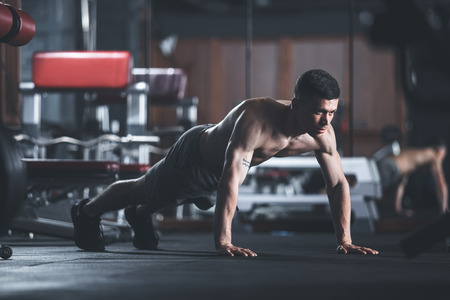 Concentrated ripped guy is exercising in sport center. He is staying in static position while doing plank. Shirtless male is balancing on feet and hands