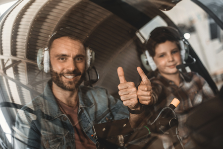Portrait of beaming dad and smiling kid demonstrating symbol cool while gesticulating hands. They looking at camera while locating in cabin of helicopter Banco de Imagens
