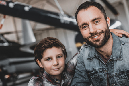 Portrait of beaming kid embracing cheerful unshaven dad while they looking at camera. They locating indoor. Positive father having leisure with son concept