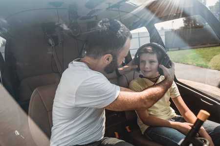 Happy male pilot putting headset on cheerful kid. They locating inside of rotorcraft during communication Stock Photo