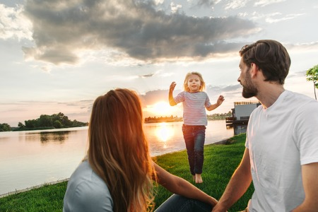 Positive child running while gesticulating hands. Outgoing father and mom watching at her while having leisure on grass outside Banco de Imagens