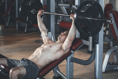 Strong sportsman is exercising with machine and barbell. He is lying on bench and lifting weight. Training with equipment concept