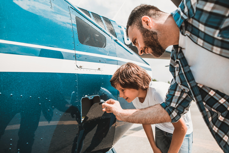 Side view beaming interested boy with attractive smile and happy unshaven father looking at fuel tank of rotor plane outdoor Фото со стока