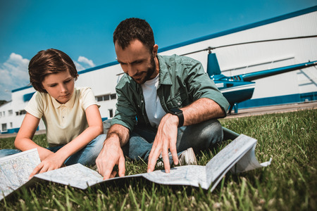 Portrait of calm kid and beaming bearded father looking at map while resting on green field during sunny day Stock fotó