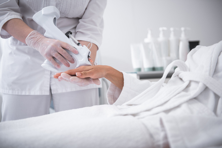 Day at beauty salon. Beautician in sterile gloves using electronic gin with syringe while girl in white bathrobe lying on daybed 版權商用圖片 - 107143959