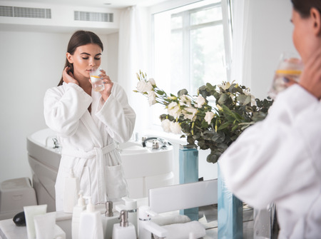 Portrait of calm girl with closing eyes tasting appetizing mug of liquid while wearing bathrobe after taking bath. She reflecting in mirror in room Stock Photo