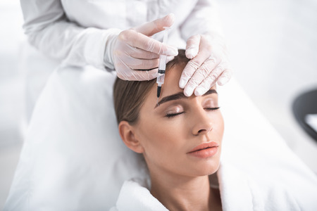 Rest and care. Close up portrait of attractive girl with closed eyes and cosmetologist hands in gloves. Doctor touching lady forehead and using syringe