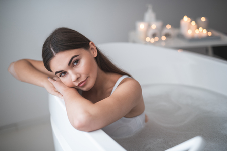 Portrait of pensive girl lying in warm water during treatment. She looking at camera. Healthcare concept Stock Photo